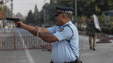 An Indian police officer aims his gun before firing at stone throwing protesters in Gauhati. No one was hurt in that firing.
