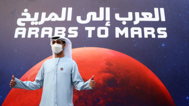 A man poses for a picture in front of a promotional poster in Dubai, United Arab Emirates.