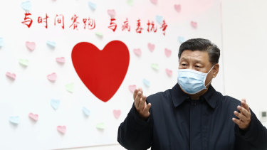 """Chinese President Xi Jinping next to a heart-shaped sign and the slogan """"Race against time, fight the virus""""."""