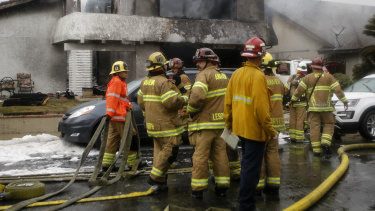 Firefighters outside one of the wrecked homes in Yorba Linda, California.