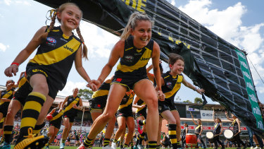 Staying positive: Katie Brennan and the Richmond AFLW mascots run through the banner before the start of the game against the Kangaroos at Ikon Park in Melbourne.