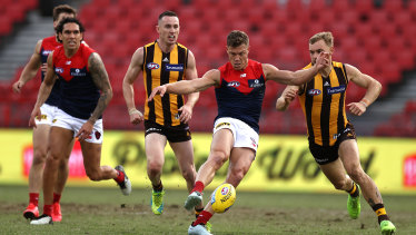 Kicking on: Jake Melksham helps the Demons surge forward against Hawthorn at Giants Stadium in Sydney.
