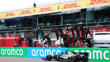 Mercedes GP team members celebrate on the pitwall as Lewis Hamilton crosses the finishing line.