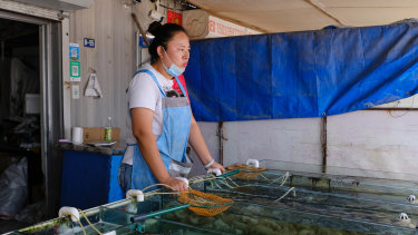 Zhang Meng waits for customers at her seafood shop in Beidaihe.
