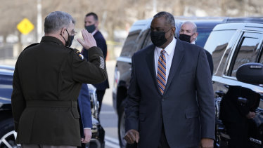 Defence Secretary Lloyd Austin, right, is saluted by Chairman of the Joint Chiefs of Staff Mark Milley as he arrives at the Pentagon.