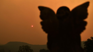 The sun is blocked by smoke rising from the Gospers Mountain bushfire.