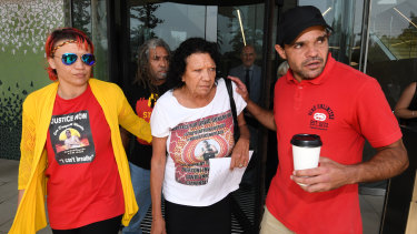 Leetona Dungay (centre) is supported at the NSW Coroners Court on Friday.