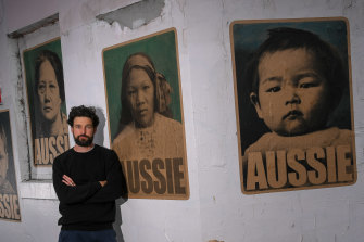 Peter Drew in front of his new posters featuring women and children who were born in Australia but had to get exemptions to travel because of the White Australia Policy.