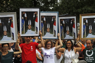 Protesters in Bayonne, south-west France,  hold upside down portraits of President Emmanuel Macron. The portraits have been removed from town halls by activists.