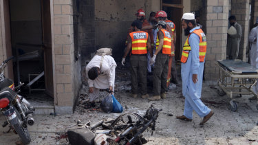 Pakistani security officials and rescue workers gather at the site of a bombing on an entrance of a hospital in Dera Ismail Khan on Sunday.