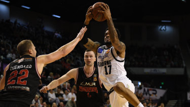 United's US import DJ Kennedy looks for a shot despite pressure from Tim Coenraad of the Hawks.