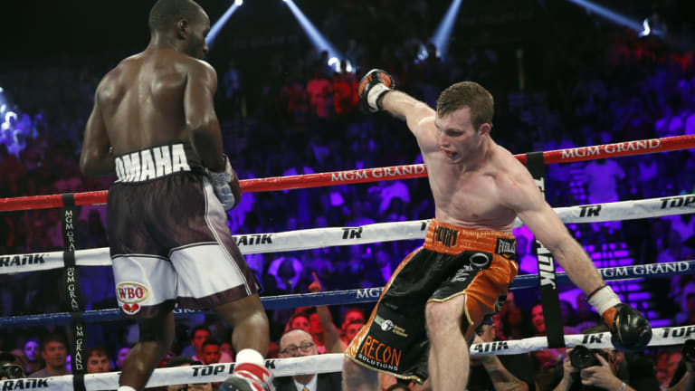 Terence Crawford, left, knocks Jeff Horn, of Australia, off balance.