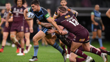NSW halfback Nathan Cleary is brought down by Queensland's Tim Glasby (left) and Josh Mcguire.
