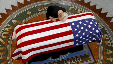 John McCain's wife, Cindy, lays her head on the casket of her husband during a memorial service at the Arizona Capitol on Wednesday.