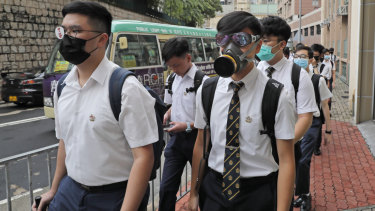 Coming as they are: students wear gas masks while dressed in their formal white school uniforms.