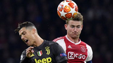 Matthijs de Ligt fights for the ball with Juventus' Cristiano Ronaldo, who is now his teammate.