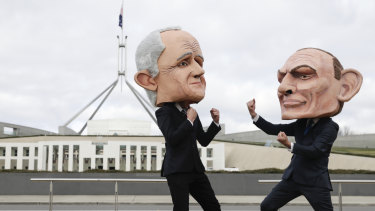 Puppets of Malcolm Turnbull and Tony Abbott pose for photographers during a renewable energy event organised by GetUp on the lawn of Parliament House on Tuesday morning.