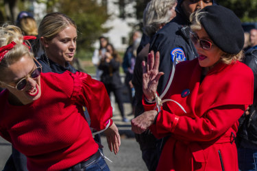 Alpha-gran Jane Fonda (right) high-fives a fellow activist after they were arrested during a rally on Capitol Hill.