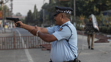 An Indian police officer aims his gun before firing at stone throwing protesters in Gauhati, India. No one was hurt in that firing.