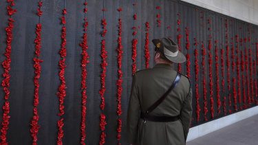 A man in uniform walks along the Roll of Honour at the Australian War Memorial.