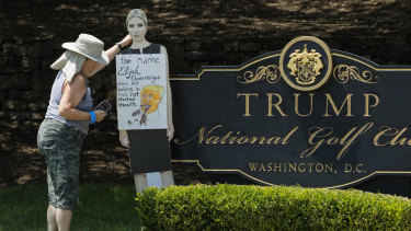 A woman places a cutout picture of Ivanka Trump outside the Trump National Golf Club in Sterling, Virginia, to protest against her father's comments on Elijah Cummings.
