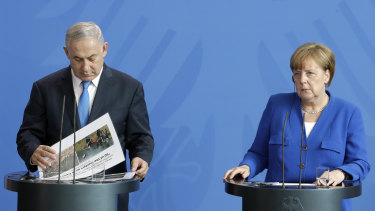 German Chancellor Angela Merkel, right, and Israeli Prime Minister Benjamin Netanyahu, left, address the media during a joint press conference as part of a meeting at the Chancellery in Berlin.