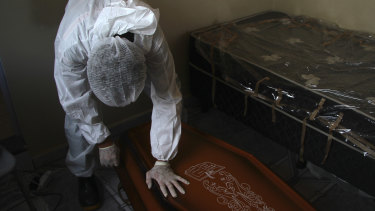 A public funeral service worker helps to remove the body of a man who died from complications related to COVID-19 in his home, in Manaus, Amazonas state, Brazil.