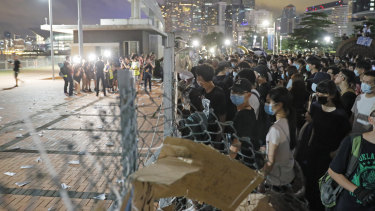 Anti-extradition bill protesters try to walk across the fence at the Central Waterfront in Hong Kong on Saturday.
