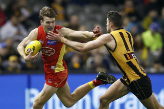 Gold Coast's Charlie Ballard fends off a tackle.