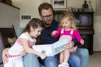 Andrew Kennedy at home, reading to daughters Isla, 5, and Hope, 2.
