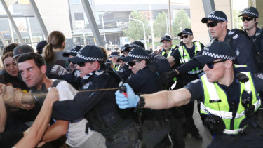 Police use pepper spray as protesters attempt to stop conference members entering the conference.