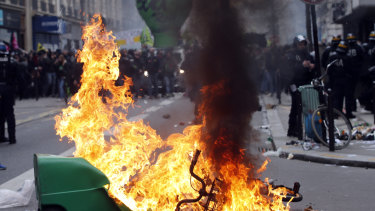 French riot police stand next a burning rubbish bin during the protests in Paris.