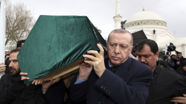 Turkish President Recep Tayyip Erdogan, centre, carries a coffin as he joins hundreds of mourners at the funeral of nine members of one family killed in the collapsed apartment building in Istanbul.