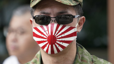 A man at at the Yasukuni Shrine in Tokyo wears a mask with a design of Japan's rising sun flag.