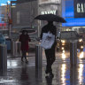 Shoppers walk in a rainstorm through New York's Times Square.