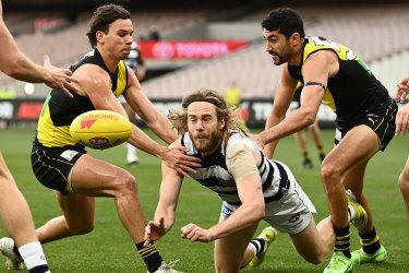 Geelong's Cam Guthrie fires off a handball against Richmond.