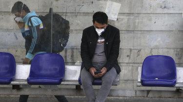 A man waits at a bus stop in Niavaran, northern Tehran, where officials have begun easing the lockdown.