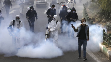 Firefighters disinfect a square against the new coronavirus in western Tehran, Iran.
