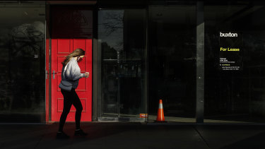 A woman walks past an empty shop on Chapel Street in Prahran.