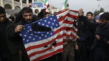 Protesters burn an American flag during a demonstration over the US killing of Qssem Soleimani in Tehran on Friday.