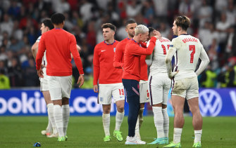 England's Phil Foden consoles teammate Jadon Sancho after he misses the side's fourth penalty