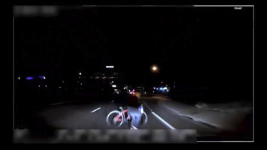 A camera inside the car shows a woman pushing a bicycle across the road in the dark.