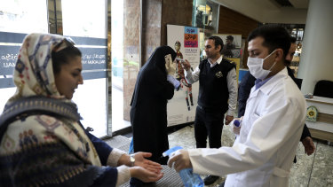 People have their temperature checked and their hands disinfected as they enter the Palladium Shopping Center, in northern Tehran, Iran.