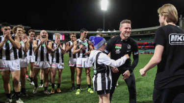 Magpies head coach Nathan Buckley celebrates victory with sons Ayce Buckley (L) and Jett Buckley (R) after coaching his final game.
