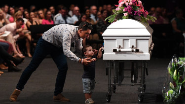 Hannah Clarke's brother Nat holds his son Tyler as he reaches for the coffin.