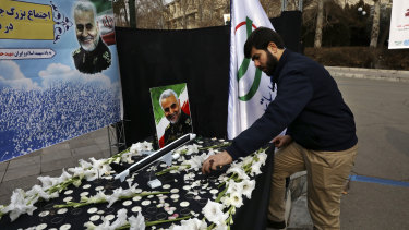 A man lights a candle at a gathering to commemorate the late Iranian General Qassem Soleimani.