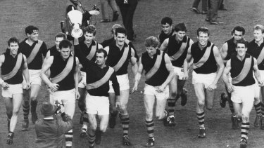 Led by captain Fred Swift, the victorious Richmond team runs a lap of honour after winning the premiership.