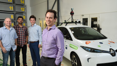 QUT Professor Michael Milford (front) and his team with the test vehicle that is trialling autonomous vehicle sensors and cameras.