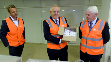 Prime Minister Scott Morrison, with Simon Buensch, executive director of manufacturing at CSL, and Dr Brian McNamee, chairman of CSL board, holds a box of AstraZeneca vaccines at the CSL factory in Melbourne last month.