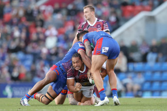 Manly's Martin Taupau is wrapped up by the Knights defence.